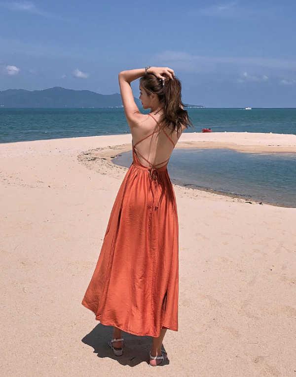 สาวสวยในชุดเที่ยวทะเลสีส้มน้ำตาลโชว์แผ่นหลัง