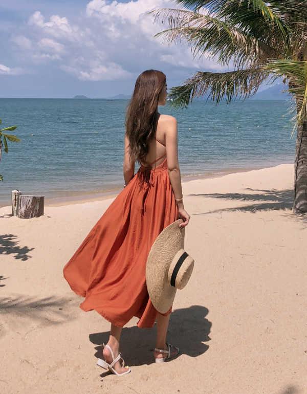 สาวสวยในชุดเดรสยาวสีส้มน้ำตาลเดินที่ทะเล
